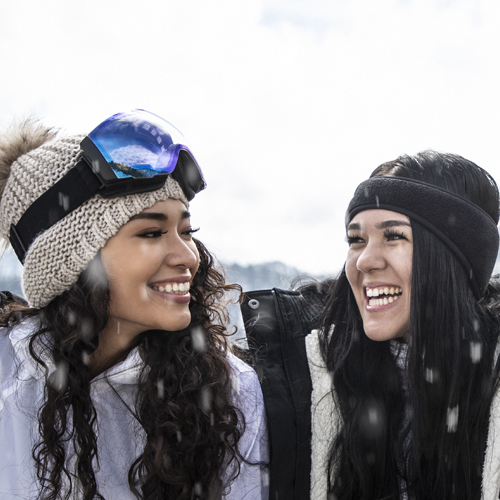 two women smiling on the ski slope