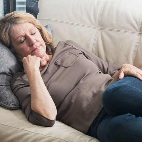 mature woman falling asleep on the couch