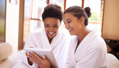 Two women lat spa watching something on a tablet.