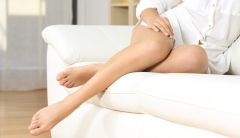 Woman's smooth, youthful legs sitting on a couch