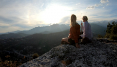 2 women watching the sunset from a mountain top.