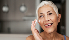 mature woman putting moisturizer on dry skin