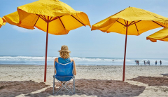 Woman sits in shade at the beach with a wide brimmed hat on.