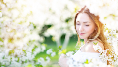 Bride looking over her shoulder amongst flowering trees