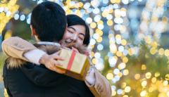 asian couple hugging and giving christmas gifts