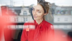 Woman in red shirt looks out of window