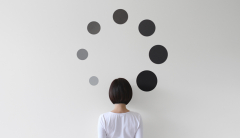 Woman facing wall surrounded by black spots