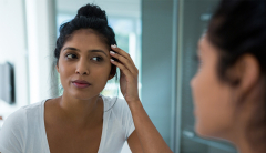 Woman worried about skin and looking in mirror