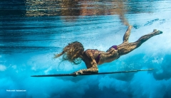 Woman diving underwater on a surfboard
